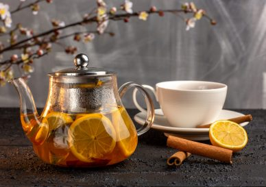 front-view-cup-tea-with-lemon-cinnamon-kettle-grey-surface